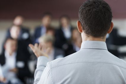 Rear view of a business man giving a speech at a seminar